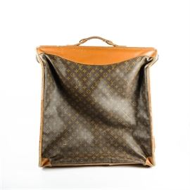 """Vintage Louis Vuitton Garment Bag: A vintage Louis Vuitton garment bag. This foldable hanging suit bag features the iconic monogram print coated canvas and light brown leather accents. It is monogrammed with the letters """"M.W.C."""" near the handle. A tag present to the interior indicates that the piece was made in the United States under license by The French Company."""