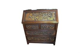Carved Asian Secretary Desk: A carved Asian secretary desk. The desk features four drawers beneath a secretary style folding desk. The desk portion has sections for papers within. The piece features scenes of Asian antiquity carved throughout.
