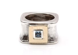 Sterling Silver 14K Gold Accented Blue Topaz Ring: A square hammered sterling silver band is enhanced by a yellow gold square accent to the center with bezel set blue topaz.