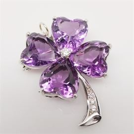 14K White Gold Amethyst Four-Leaf Clover Brooch/Pendant: A 14K white gold amethyst and diamond four-leaf clover brooch/pendant. This brooch features four amethyst heart-shaped stones with a diamond center and diamond embellished stem. It includes a purple box.