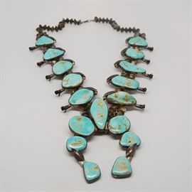 Vintage Native American 800 Silver Turquoise Squash Blossom Necklace: A vintage Native American 800 silver turquoise squash blossom necklace. This heavy necklace features a double strand of handmade etched seed beads with turquoise stones designed with squash blossoms and leaf detailing.