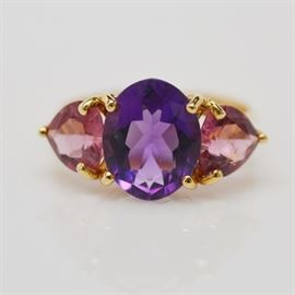 14K Yellow Gold Amethyst and Pink Tourmaline Ring: A 14K yellow gold amethyst and pink tourmaline ring. Ring features a basket set center oval amethyst and two side heart-shaped pink tourmaline.