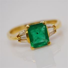 18K Yellow Gold 1.79 Cts Emerald and Baguette Diamond Ring: An 18K yellow gold emerald and baguette diamond ring. This emerald cut emerald is basket mounted with accent baguette diamonds.