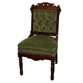 Antique Eastlake Style Mahogany Side Chair: An antique Eastlake style mahogany side chair. The side chair features a carved shell medallion with openwork and scrolling foliate designs along top rail, olive green velvet upholstery to the seat and tufted back, faceted brass rivet detailing bordering the back and carved apron, and front turned legs.