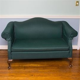 Emerald Green Upholstered Satin Loveseat: An emerald green satin upholstered loveseat. The loveseat features an undulating back, rolled arms, removable armrest covers and seat cushion, and walnut cabriole front legs. The loveseat is upholstered in an emerald green satin fabrication with tonal stripes throughout.