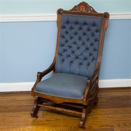 Antique Eastlake Style Mahogany Gliding Rocking Chair: An antique Eastlake style mahogany gliding rocking chair. The rocking chair features carved medallions with openwork and scrolling foliate designs along top rail, a cotton jacquard upholstery to the seat and tufted back in a shade of cerulean blue with a cream accented fan print throughout, sloping arms, curved base, turned supportive stretcher, and metal casters on front legs.
