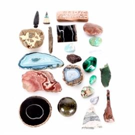 """Natural and Man-Made Mineral Collection: A natural and man-made mineral collection. Featuring twenty-three unique stone pieces including a smooth stone sphere and a pyramid shaped stone marked """"Made in Brazil"""". Also included are a rock with carved designs, marked on the back """"UGARIT ALPHABET 1400 BC"""", a black arrowhead and another stone tool, several colorful polished stones, and polished stone cross-sections."""