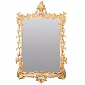 Large Chippendale-Style Gilded Mirror: A large Chippendale-style gilded mirror. Featuring a gold tone finish to its wood and gesso frame, this large wall mirror includes scroll and floral work throughout. The mirror also includes hanging hardware to the verso.