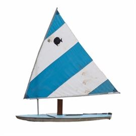 Alcort Sunfish Sailboat: An Alcort Sunfish sailboat. Included is a personal-sized sailboat with a fiberglass boat frame and down-wind sail. The Sunfish was originally introduced by Alcort in 1952. This boat has a blue coloring with an alternating stripe pattern along the sail of blue and white.