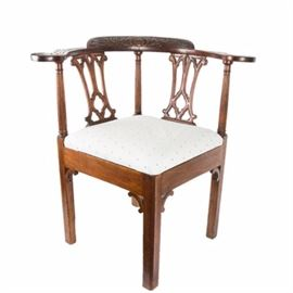 Mahogany Chippendale Style Corner Chair: A mahogany Chippendale style corner chair. This early 20th century mahogany chair features a carved top rail with a wheat and shell design and quatrefoil splats. Other features include an upholstered drop in seat, an apron with scrolled brackets tied into straight wood legs. The upholstery is a white damask cloth with a blue spherical pattern.