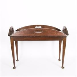 Queen Anne Style Butlers Coffee Table: A Queen Anne style butler's coffee table. This mahogany table features an oval shape with pierced leaves that fold up with brass hinges, to form a tray top. The paneled surface resting on an tapered legs terminating in pad feet.