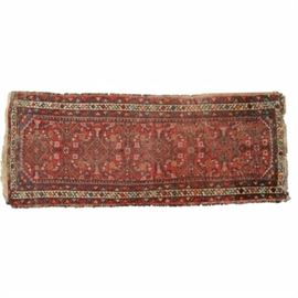 Hand-Knotted Persian Carpet Runner: A hand-knotted Persian carpet runner. This rug features a geometric pattern in greens, blues, pinks, oranges, and cream over a red ground color. The simple border displays colorful circles connecting by a scrolling vine on a cream backdrop. Cream fringe appears at either end. There is no maker's mark or label present.