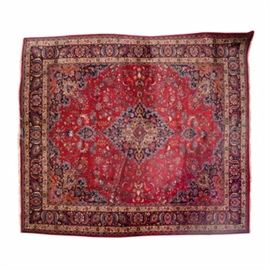 Hand-Knotted Persian Mashad Area Rug: A hand-knotted Persian Mashad area rug. The rug features a central medallion in a palette of indigo, red, cream, and powder blue that sits on top of a deep red field. The field is covered in arabesque linework, floral palmettes and offers a spandrel to each corner, also filled with floral patterns in a matching palette. The field is enclosed inside of a compound resolved border with a herat pattern in a matching palette that showcases palmettes and vinework that sit on top a deep indigo background. The rug features a wool fringe to either end and is not marked.