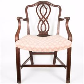 Sheraton Style Mahogany Armchair: A vintage Sheraton-style mahogany armchair. This armchair features a mahogany finish, a pierced, serpentine splat, burgundy, peach, salmon floral-patterned fabric upholstery, and Marlborough legs. There are no other visible makers markings or labels on this chair.