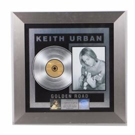 Keith Urban Platinum Record: A Keith Urban platinum sales award. Presented by the Recording Industry Association of America, this piece commemorates 1,000,000 copies sold of Urban's album Golden Road with a metal nameplate at the base awarding it to Dann Huff. The piece is presented under glass in a silver tone metal frame with a wire wall hang to the back.