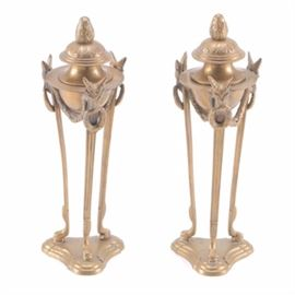 "Pair Of Brass Candle Holders: A pair of brass candle holders. These pieces were made in India and follow a classical design with covers, and swags. There are three supports anchoring the top to the stepped bases. There is a decal on the reverse reading ""TIC Made in India""."