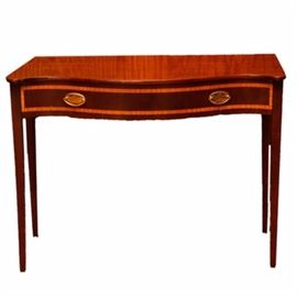 Regency Style Console Table: A Regency style console table. This table features a mahogany finish with inlay and brass-toned drawer pulls. The top and the single drawer have serpentine fronts. The table rises on four tapered legs.