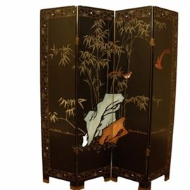 Asian Inspired Room Divider: An Asian inspired room divider. This four-panel wooden room divider is painted black on one side and yellow on the other, brass-tone metal hardware, and features a low relief carved and painted imagery of rocks with bamboo spanning the background with various birds throughout and a floral geometric border. The divider rests on eight legs with brass tone metal accents.