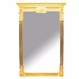 Ornate Wall Mirror: A rectangular wall mirror. This mirror features a gilded finish, acanthus leaf decoration, and a beaded edge. There are molded lions heads at the corners and beveled glass.