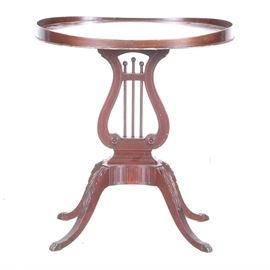 Wooden Harp Style Table: A wooden harp style table. This oval accent table has a mahogany colored stained finish. It has a raised edge to the top, carved details to the legs and petite claw feet.