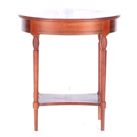 "Vintage Wood End Table: A vintage wood end table. This side table features a cedar polished finish, with a black borders on the top and around the base. It is marked, ""Made in Spain."""