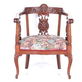 Antique Armchair: An antique armchair. This chair features a mahogany stained wooden frame which has intricate carved details. It rests on petite cabriole style legs and has a cushioned seat which is upholstered in a floral fabric.