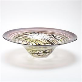 N.W. Goodson Purple Art Glass Bowl: A N.W. Goodson purple art glass bowl. This wide rimmed art glass bowl features a swirled design of purple and green. It is signed to the bottom with the artist and dated 9/89.