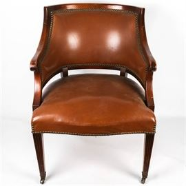 Regency Barrel Back Chair: A regency style barrel back chair. The chair is upholsters in brown faux leather with brass nail head details. The front legs rest on brass tone casters.
