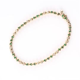 14K Emerald and Diamond Tennis Bracelet: A 14K yellow gold emerald and diamond tennis bracelet.
