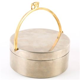 Gucci Lidded Candy Dish: A Gucci lidded candy dish. The round, lidded dish is silver tone in color with gold tone accents. The piece was made by Gucci as indicated by the plaque affixed to the front of the piece as well as the stamp present to the underside. The handle of the dish resembles a snaffle bit, a signature motif of Gucci.