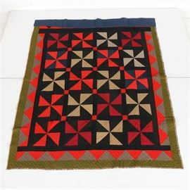 Handmade Pinwheel Pattern Quilt: A handmade pinwheel pattern quilt. This blanket features red, orange, and off-white pinwheel patterns to the body on a black and green backdrop with an orange-pink and gray triangular border with green and blue outlines. The underside is plaid.