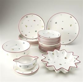 """Gmundner """"Scattered Blooms"""" Tableware: A selection of Gmundner Scattered Blooms tableware. This selection features one serving platter, one serving bowl, one star shaped serving bowl, six soup bowls, six salad plates, four dinner plates, and one gravy boat with drip tray. Each item features the Scattered Blooms pattern and is marked Gmundner Keramik Made in Austria"""" on the bottom."""