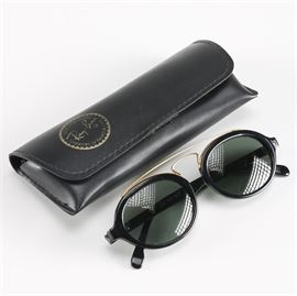 """""""Gatsby"""" Ray-Ban Sunglasses: A pair of Gatsby Style Ray-Ban sunglasses. The round black frames feature gold colored framework and are accompanied with a Ray-Ban protective case. The temples of the sunglasses are marked """"Gatsby Style 6 W0940 B & L Ray-Ban""""."""