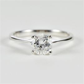 Solitaire Diamond Ring: An 18K white gold and solitaire diamond wedding ring. This classic style features a 0.98 carat round brilliant cut diamond in a 4-prong setting.