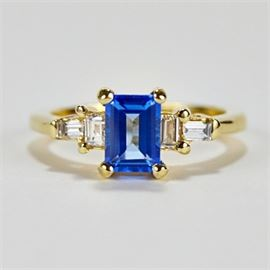 Blue Topaz and Diamond Engagement Ring: A blue topaz and diamond engagement ring set in 14K yellow gold.