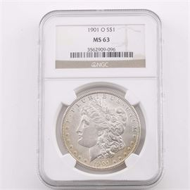 Graded MS63 (By NGC) 1901 O Silver Morgan Dollar: An encapsulated and graded MS63 (By NGC) 1901 O silver Morgan dollar. Designer: George T. Morgan. Mintage: 13,320,000. Metal content: 90% silver, 10% copper. Diameter: 38.1 mm. Weight: 26.7 grams. Very good condition.