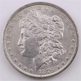 1879 Silver Morgan Dollar: An 1879 silver Morgan dollar. Designer: George T. Morgan. Mintage: 14,806,000. Metal content: 90% silver, 10% copper. Diameter: 38.1 mm. Weight: 26.7 grams. Very good condition.