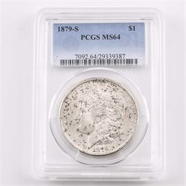 Graded MS64 (By PCGS) 1879 S Silver Morgan Dollar: An encapsulated and graded MS64 (By PCGS) 1879 S silver Morgan dollar. Designer: George T. Morgan. Mintage: 9,110,000. Metal content: 90% silver, 10% copper. Diameter: 38.1 mm. Weight: 26.7 grams. Circulated. Very good condition.