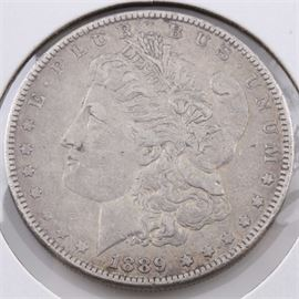 1889 Silver Morgan Dollar: An 1889 silver Morgan dollar. Designer: George T. Morgan. Mintage: 21,726,000. Metal content: 90% silver, 10% copper. Diameter: 38.1 mm. Weight: 26.7 grams. Circulated. Good condition.