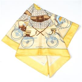 """Hermès """"Les Voitures a Transformation"""" Silk Scarf: An Hermès silk scarf. This 100% silk scarf features the Les Voitures a Transformation pattern depicting a carriage seat, a bicycle with a seat and an automobile in blue, gray, golden yellow and brown hues with a vivid yellow border. The pattern was originally designed by Françoise De La Perriere in 1965. The edges of this piece are rolled and hand-stitched. Made in France."""