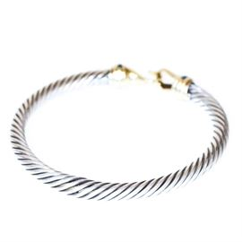 David Yurman Sterling Silver and 14K Yellow Gold Bangle Bracelet: A David Yurman sterling silver and 14K yellow gold bangle bracelet. This bracelet features a sterling silver twisted cable style design finished with crystal accents and 14K yellow gold caps with a hook and eye closure.