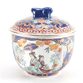 Japanese Porcelain Bowl with Lid: A small ceramic bowl manufactured in Japan, it comes with a lid and is painted in hues of blue, green, red, yellow, orange, and beige. The side of the bowl depicts two women sitting in a Japanese garden and both the bowl and the lid are decorated with floral designs and scroll work. The handle of the lid is shaped like a bear. The bottom of the bowl bears the manufacturer's mark in orange.