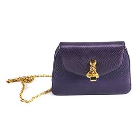 Judith Leiber Crossbody Bag: A Judith Leiber crossbody bag. The purple textured leather handbag features a gold colored crossbody chain, three purse keychains in the center of the bag, and a tiny gold colored comb and compact duo. The handbag is accompanied with a dust cover.