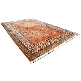 Hand Loomed Indo-Persian Area Rug: A handwoven Indo-Persian area rug. This large wool rug features an allover arabesque pattern of shah abbasi palmettes, floral sprays, and lancet leaves over an orange field. The field is framed by eight borders, including a main border of palmettes surrounded by daisies and a Meda Hil outer guard border. The palette is orange, shades of blue, ivory, and tan. The rug finishes in ivory cotton fringe at either end, with overcast edges on the sides. It is unmarked.