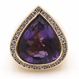 14K Yellow Gold Amethyst and Diamond Ring: A 14K yellow gold amethyst and diamond ring. This ring features a pear shaped amethyst cabochon with a diamond border in a thick yellow gold shank.