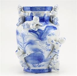 Chinese Porcelain Vase with Babies: A hand-painted porcelain vase made in China, the vase is made from glossy white porcelain and is painted in a blue finish. There are six figurines of Chinese infants that adorn the vase, and the depictions along the sides included fish, wildlife, and plants. The vase has a hexagonal opening at its top, and there is a manufacturer's mark on the bottom of the vase.