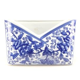 Porcelain Chinese Letterbox: A unique Chinese letterbox made of porcelain, the piece is white and is decorated with blue floral designs, white waterfalls, and a sweeping blue border at the rim. The letterbox has a triangular stand on its back to provide stability.