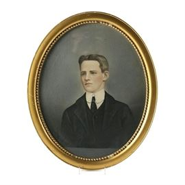 Early 20th Century Colored Pencil on Paper Portrait of Young Man: An early 20th century colored pencil portrait on paper. The framed piece depicts a young man in turn-of-the-century attire. The subject wears a black suit with matching vest and tie over a high-collared white shirt. The unsigned piece is presented under glass in an oval gold tone frame with beaded accents to the inner perimeter. The frame does not include hanging wire or brackets.