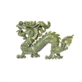 Carved Jadeite Dragon: A carved jadeite serpentine dragon. It is in the form of an Asian style dragon with claw feet and etched scales along the body. There are no marks.