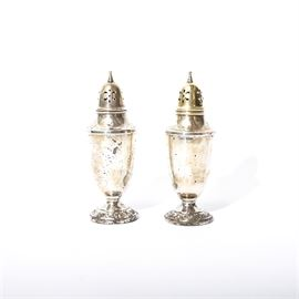Towle Sterling Silver Salt and Pepper Shakers: A set of Towle sterling silver salt and pepper shakers. They are in the French provincial style with fluted bodies resting upon round footed bases. The tops are pierced holes at the top and conical finials. The bases are embossed with a filigree pattern.